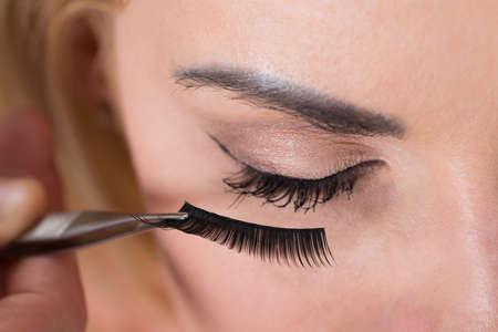 Close-up van valse wimpers op het oog van de vrouw wordt gebracht