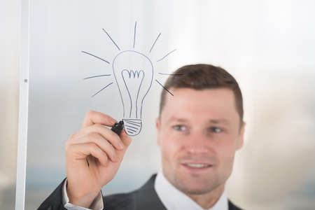 adult wall: Smiling mid adult businessman drawing lightbulb on glass wall in office