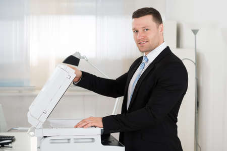 photocopy: Side view portrait of businessman using photocopy machine in office Stock Photo