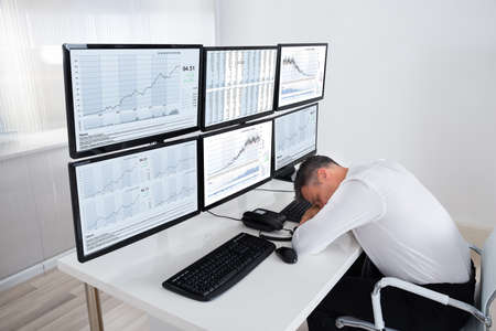 computers office: Mature male stock trader sleeping at multiple computers desk in office