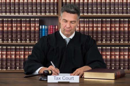 Belasting rechtbank naambord op tafel met de rechter schrijven op papier tegen boekenplank in rechtszaal