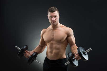 musculoso: Retrato de hombre musculoso confía en la celebración pesas mientras está de pie contra el fondo negro