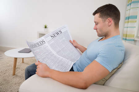 classifieds: Mid adult man reading newspaper on sofa at home
