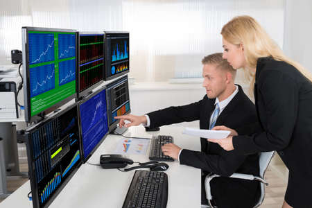 Young financial agents monitoring computer screens at desk in office