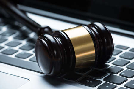 government regulations: Closeup photo of mallet on laptop keyboard Stock Photo