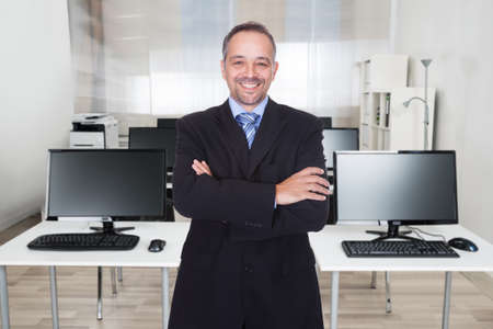 Portrait of confident mature businessman standing arms crossed in office photo