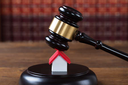 authority: Closeup of wooden mallet being hit on house model at table in courtroom