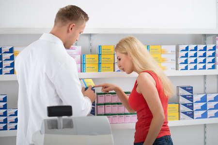 preguntando: Mujer joven que discuten sobre medicamentos con farmacéutico por los estantes en la tienda Foto de archivo