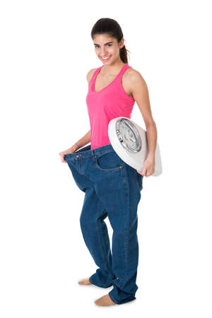woman on scale: Smiling young woman with weight scale showing her old jeans after diet on white background Stock Photo