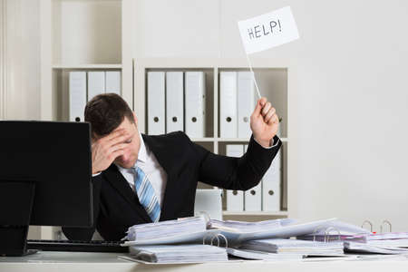 Overworked accountant holding help sign while working at desk in office Stock Photo