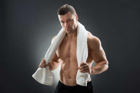 toallas: Hombre muscular que sostiene una toalla alrededor del cuello mientras está de pie contra el fondo negro