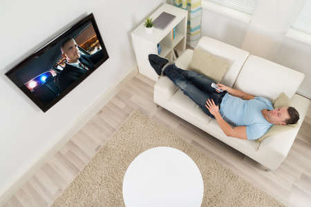 angle: High angle view of mid adult man watching movie on television in living room Stock Photo