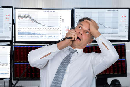 business problems: Sad mature stock trader with hand on head using telephone in office