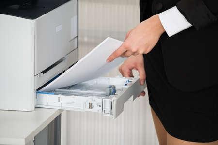 fotocopiadora: Sección media de los papeles de la empresaria en la inserción de la fotocopiadora en la oficina Foto de archivo