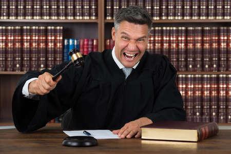 Retrato de juez madura enojado golpeando con el martillo en la mesa de sala