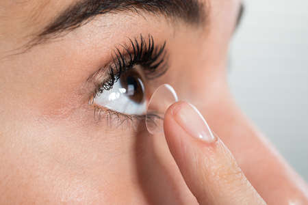 prescribed: Closeup of young woman wearing contact lens at home Stock Photo