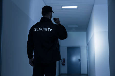 security uniform: Rear view of security guard with flashlight in building corridor