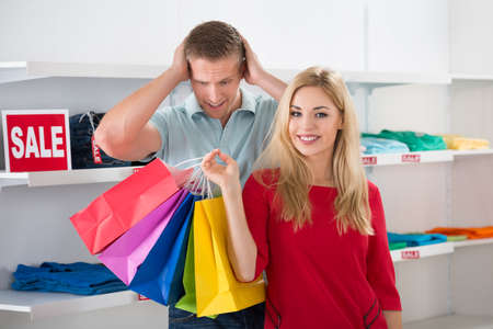 sale tag: Shocked young man looking at woman carrying colorful shopping bags in store