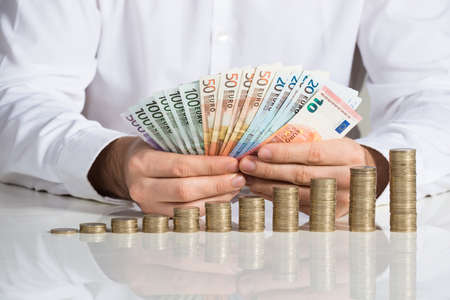 fanned: Midsection of businessman fanned euro notes with coins stacked at office desk