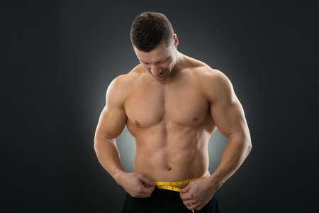 waistline: Muscular man measuring waistline with measure tape against black background Stock Photo