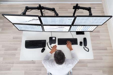 オフィスで机のグラフを見て株式市場のブローカーの背面図