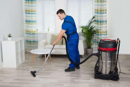 自宅の掃除機で床を掃除する男性労働者の完全な長さ