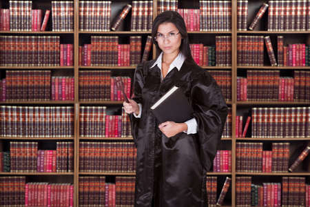 Portrait of serious female judge holding gavel and book against shelves photo