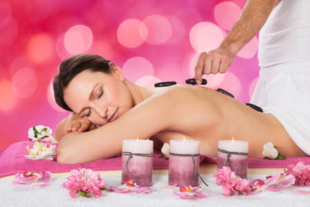 stone therapy: Relaxed young woman receiving hot stone therapy in beauty spa