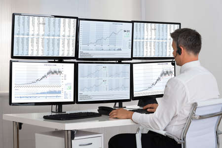 multiple: Side view of stock market broker looking at graphs on multiple screens in office