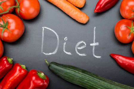 directly: Directly above shot of Diet written amidst fresh vegetables on blackboard Stock Photo