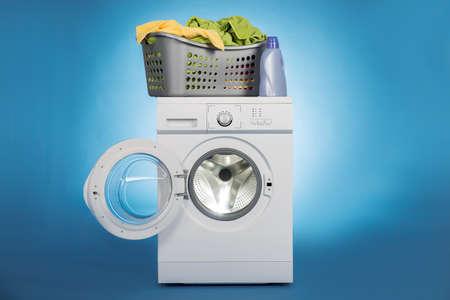 lavadora con ropa: cesto de la ropa llena de ropa sucia en la lavadora sobre un fondo azul