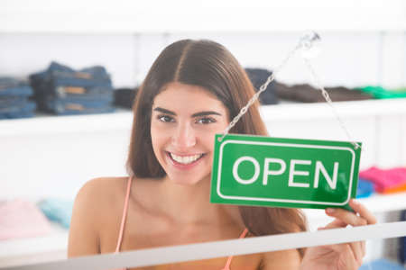 store sign: Portrait of smiling female owner holding open sign in clothing store Stock Photo