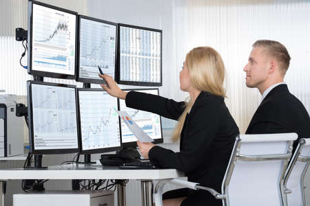 Financial workers analyzing data displayed on computer screens at desk in office Imagens