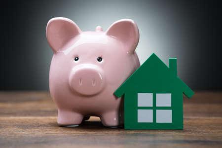 viviendas: Primer plano de la casa de papel verde y hucha en la mesa de madera sobre fondo gris Foto de archivo