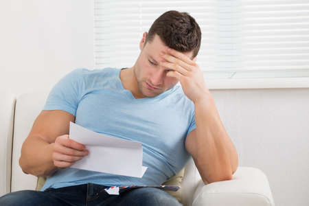 Upset mid adult man with head in hand reading letter on sofa at home