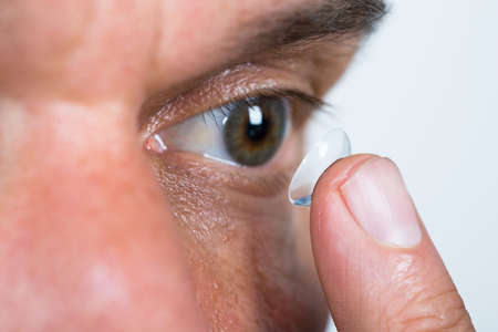 Closeup of man putting contact lens in eye over white background