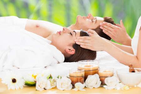 relajado: Vista lateral de la joven y masaje de cabeza pareja receptora relajado en spa de belleza