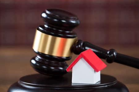 gerechtigkeit: Nahaufnahme von Holzhammer mit Haus-Modell auf dem Tisch im Gerichtssaal