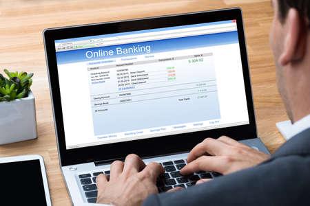 Imagen cosechada del hombre de negocios que hace actividades bancarias en línea en la computadora portátil en el escritorio de oficina