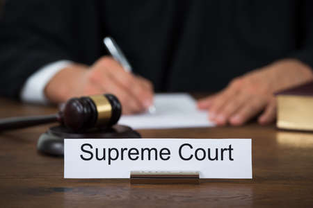 Supreme court nameplate with judge writing on paper at table in courtroom
