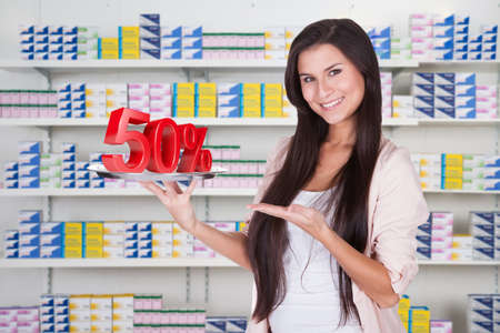 Portrait of happy saleswoman showing 50% sign at supermarket photo