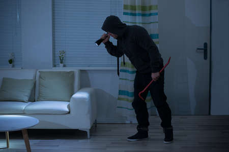 intruding: Full length of robber with crowbar and flashlight in living room Stock Photo