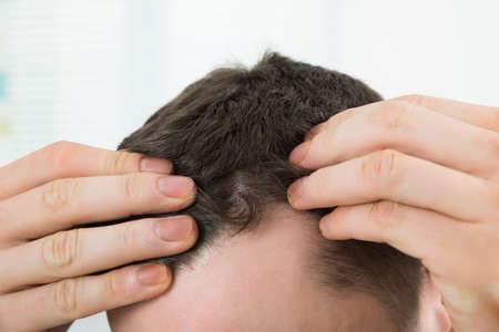 Gros plan de l'homme d'âge moyen de vérifier la racine des cheveux à la maison Banque d'images