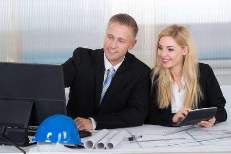 arquitecto: arquitectos jóvenes discutiendo sobre la computadora con los modelos en el escritorio en la oficina