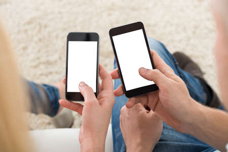 Cropped image of young couple using smart phones with blank screens at home