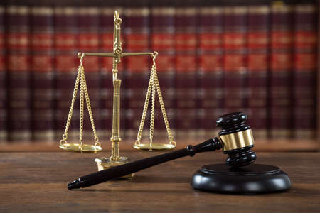 government regulations: Closeup of wooden mallet and justice scale on table in courtroom Stock Photo