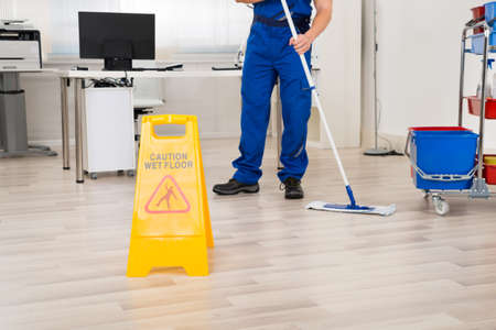 低部オフィスでモップで床を掃除する男性用務員 写真素材