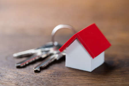 Closeup of house model and keys on wooden table