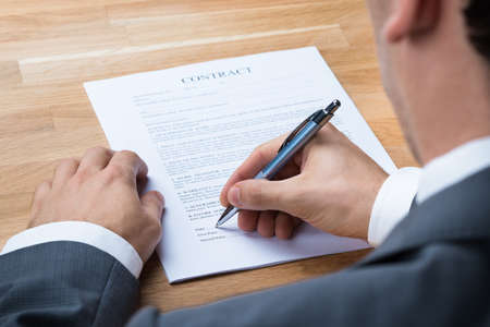 signing authority: Cropped image of businessman signing contract document at office desk Stock Photo
