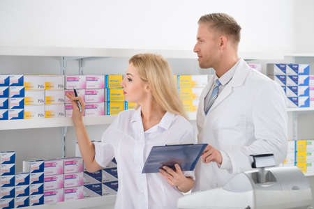 inventario: Male and female pharmacists checking inventory at pharmacy Foto de archivo